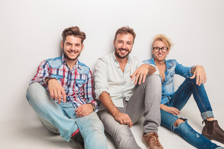 guys: happy group of men laughing for the camera while sitting down on the floor in studio Stock Photo