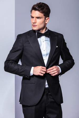 unbutton: Attractive business man looking to his side while unbuttoning his tuxedo.