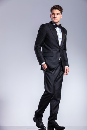 man in tuxedo: Side view of a young business man walking with his hand in pocket on studio background.