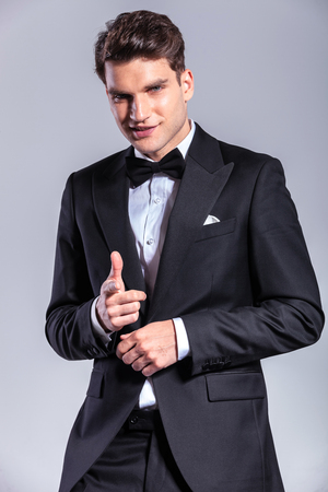 Young business man smiling while pointing at the camera. photo