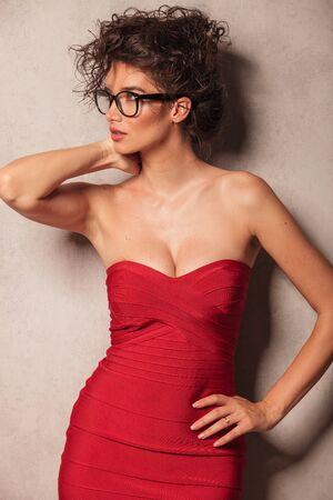 cintura: Mujer joven atractiva que mira manera mientras que presenta cerca de una pared gris.