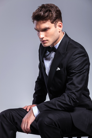 man looking down: Side view of a young elegant business man looking down while sitting.