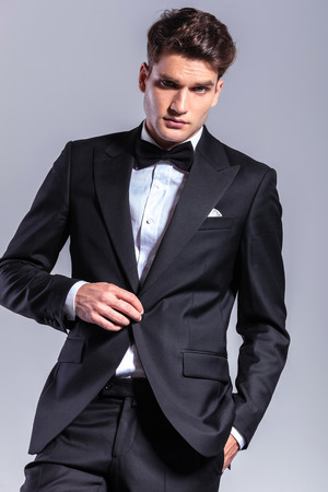 Young business man unbuttoning his jacket while holding one hand in his pocket. photo