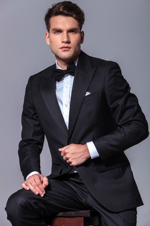 Portrait of a young business man pulling his jacket while sitting on a stool. photo