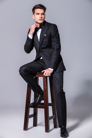 Full body picture of a elegant business man sitting on a chair while pulling his collar. photo