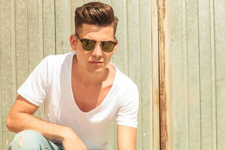 adolescent sexy: young man sitting outside with hand on his knee while wearing sunglasses Stock Photo