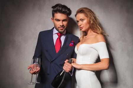 ファッションのエレガントなカップルを一緒に誕生日を祝うためにシャンパンを飲む準備ができて