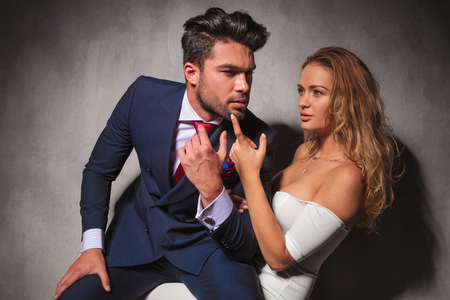 double chin: side view of a hot elegant couple sitting in studio, man is sitting on womans knees and looks away from the camera Stock Photo
