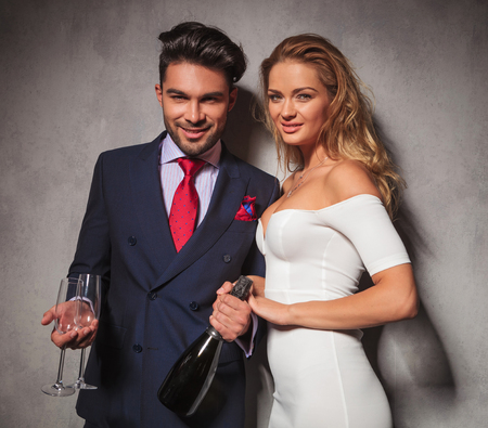 happy smiling elegant couple holding a bottle of champagne and glasses inviting you to a party 스톡 콘텐츠