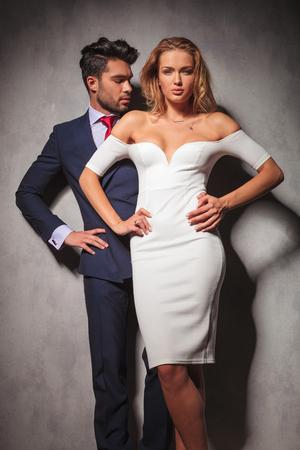 double breasted: caliente elegante pareja de moda de pie con las manos en las caderas en el estudio, mujer delante de su hombre.