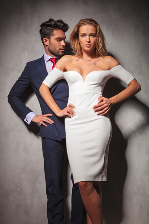 double breasted: hot elegant fashion couple standing with hands on hips in studio, woman in front of her man.