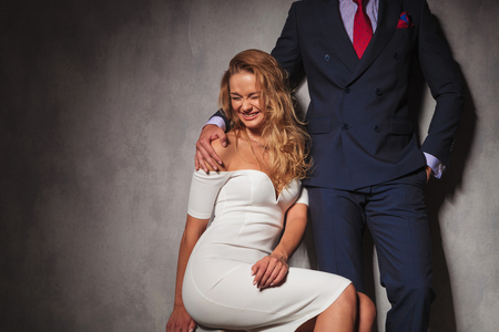 double breasted: blonde sexy woman laughing while her man is holding his hand on her shoulder, studio picture of a hot young couple