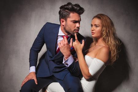 double breasted: hombre elegante est� sentado en las rodillas de la mujer atractiva rubia, ella est� sosteniendo la barbilla con el dedo. copuple sensual en estudio