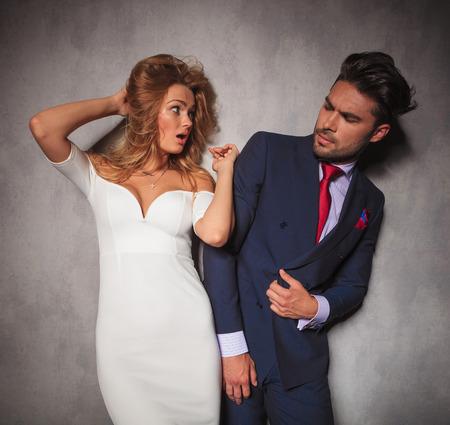 double breasted: mujer elegante joven sorprendido est� mirando a su hombre, de pie en el estudio