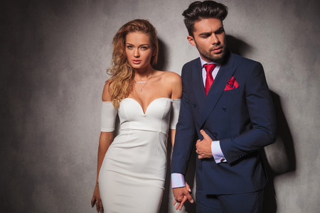 boy and girl holding hands: macho fashion elegant man holding his lover by her hand and looks to a side, sexy woman is looking at the camera in studio