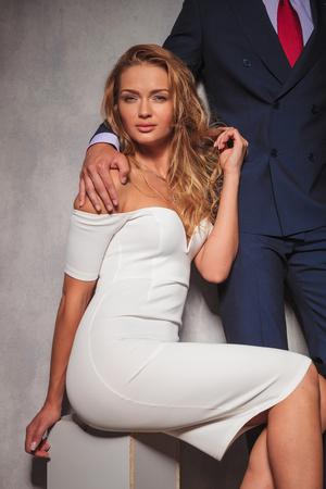 double breasted: imagen Recorte de un hombre de negocios con la mano en el hombro de su amante, la mujer en la sentada y mira a la c�mara
