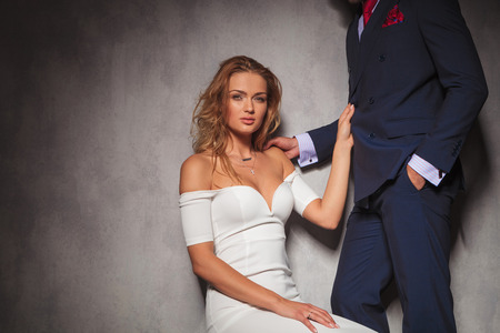 double breasted: sexy blonde woman holding her lover by his suit and looks at the camera while sitting. hot elegant couple in studio