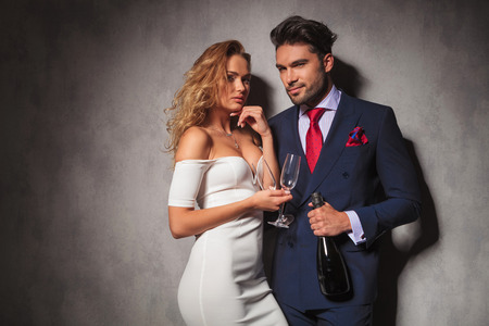 woman red dress: elegant couple ready to party with a botle of champagne in studio Stock Photo