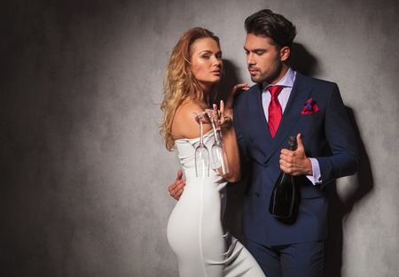side view of a hot couple holding a bottle of champagne , man is looking at his woman while she is holding two glasses Foto de archivo