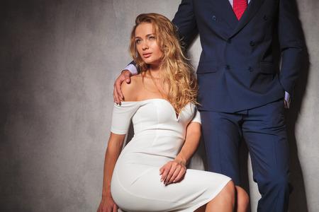 double breasted: mujer sexy en vestido blanco es que sienta y mira hacia otro lado de la c�mara mientras un se�or la est� llevando a cabo por el hombro. elegante pareja caliente en el estudio