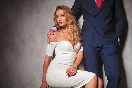 double breasted: sexy woman in white dress is sitting and looks away from the camera while a gentleman is holding her by her shoulder. hot elegant couple in studio