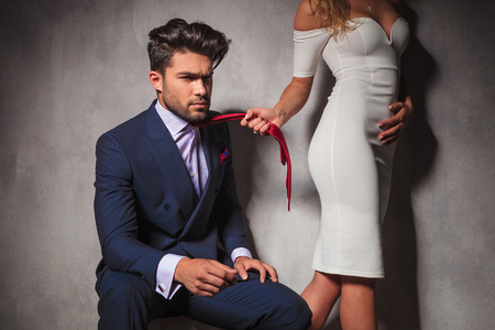 side view: sexy blonde woman is pulling her lover by his tie, man looks angry and dramatic
