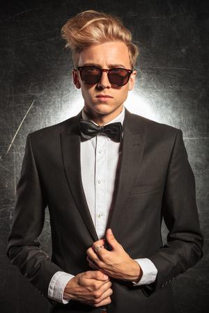 tuxedo jacket: handsome man in tuxedo posing in studio wearing sunglasses while fixing his jacket Stock Photo