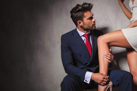 tacones rojos: verdadero caballero está ayudando a su mujer para conseguir sus zapatos mientras se está sentado. pareja sexy en el estudio