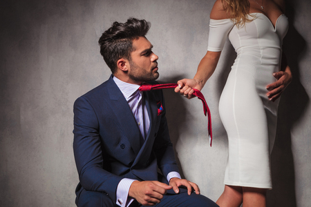 woman red dress: elegant man looking at his lover while she is pulling his tie and walks away in studio