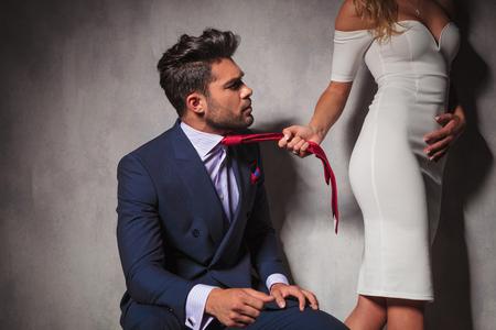 mujeres sentadas: hombre elegante mirando a su amante mientras ella está tirando de su corbata y se aleja en el estudio Foto de archivo