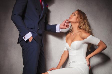 suit: sexy de un caballero que sostiene su mujer por su barbilla, que está sentado en el estudio. pareja sensual caliente en el estudio