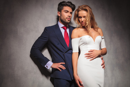 embraced elegant fashion couple standing in studio with hands on hips , man looks away to a side and woman looks down, in studio