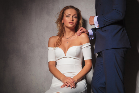 modelos hombres: imagen Recorte de un elegante pareja en estudio, la mujer est� sentada y el hombre est� sosteniendo su mano en el hombro
