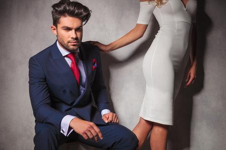 double breasted: hombre elegante joven que se sienta y su mujer lo dej�, a poca distancia en el estudio