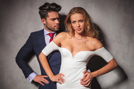 double breasted: elegant man standing behind his woman with hands on hips. Fashion elegant couple in studio posing