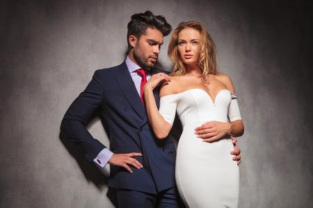 double breasted: moda hombre elegante abrazando a su mujer y mira a su anillo de compromiso, ella est� buscando fuera de la c�mara con su mano en el hombro
