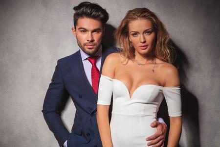 double breasted: de moda elegante pareja abrazada en el estudio, mujer delante de su amante, ambos mirando a la c�mara, el hombre con la mano en el bolsillo
