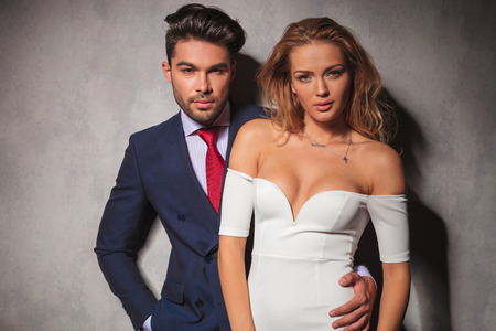 double breasted: fashion elegant couple standing embraced in studio, woman in front of her lover, both looking at the camera, man with hand in his pocket