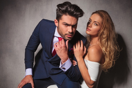 double breasted: dramatic hot elegant couple sitting embraced and looking at the camera
