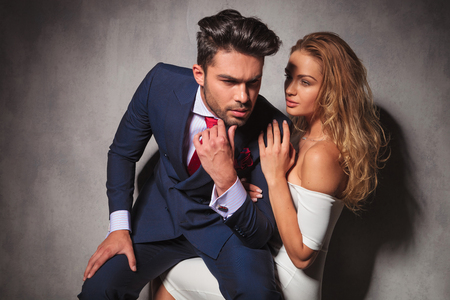 ties: woman is looking at his elegant man while he is sitting on her lap, in studio Stock Photo