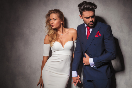 boys and girls: elegant hot couple in dramatic pose, holding hands in studio, standing against wall and looking away from the camera