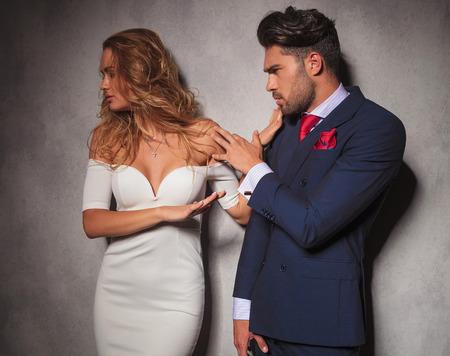 double breasted: mujer elegante est� empujando a su hombre mientras �l intenta convencerla de que, fotograf�a de estudio Foto de archivo