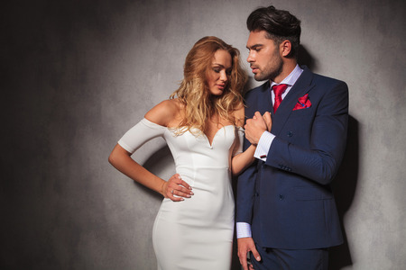 double breasted: hot sexy elegant man holds his womans hand, he is looking at her while she looks down, in studio Stock Photo