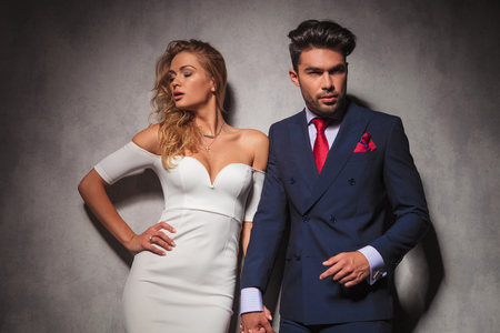 dress suit: hot elegant couple holding hands and posing in studio, he is wearing a double breasted suit with red tie and she is wearing a white dress Stock Photo