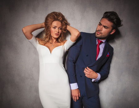 double breasted: woman holding her hair up next to her boyfriend, he is looking at her in studio