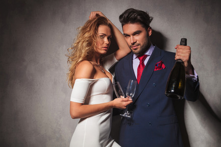 rich: sexy elegant couple with botle of champagne , posing in studio