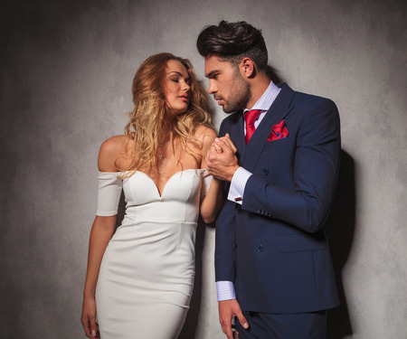 double breasted: hombre elegante sostiene su amante con pasi�n por su mano, que est�n buscando el uno al otro en el estudio Foto de archivo