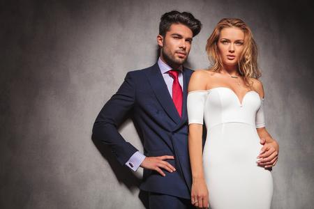 エレガントなファッションの若いカップルは、彼女の腰が彼の女性を抱きかかえた studio の中に立って、腰に手をカメラから離れて探して