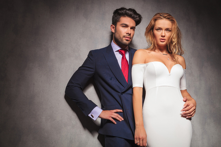 double breasted: young elegant fashion couple looking away from the camera in studio, while standing with hands on hips, man holding his woman by her waist