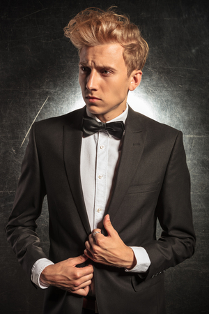 tuxedo jacket: fashionable man wearing tuxedo in studio pose looking away while fixing his jacket Stock Photo